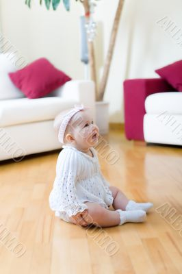 Happy eight month old baby girl seated on a hardwood floor