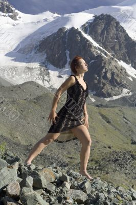 Girl in a black dress in the mountains
