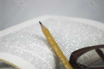 Pencil and glasses on a book