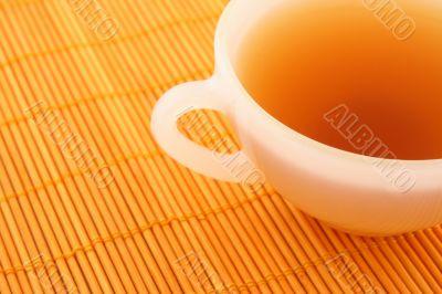 Cup of tea on orange rattan mat