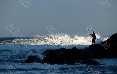 fisherman silhouette on rocks