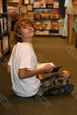 young teen boy sitting in bookstore reading