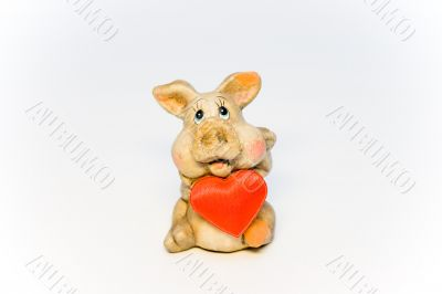 Stone figure of the pig holding red heart