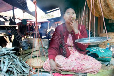 asian market seller smoking a sigar