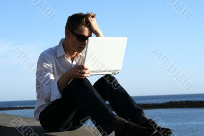 Young man with laptop at the coast sea
