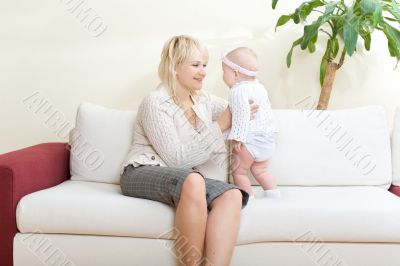 Mother and her baby girl seated on white sofa