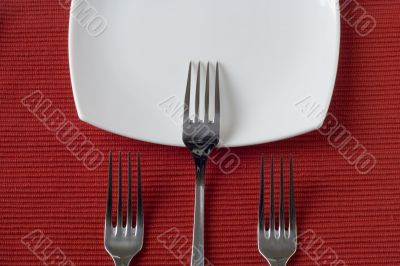 three forks and porcelain plate