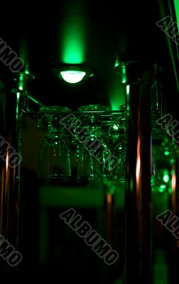 Glasses hang above a bar in green lighting