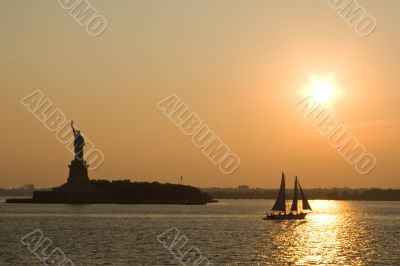 Statue of Liberty and sailing ship at sunset