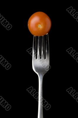 Fresh cherry tomato on a silver for against a black background