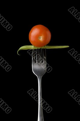 Cherry tomato and peas on fork