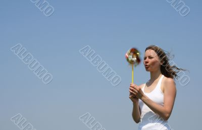 Young woman blowing a colorful pinwheel