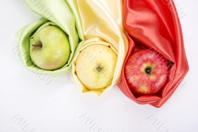 three apples of different colour wrapped in silk