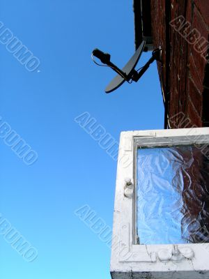 Dish-shaped antenna and window against sky