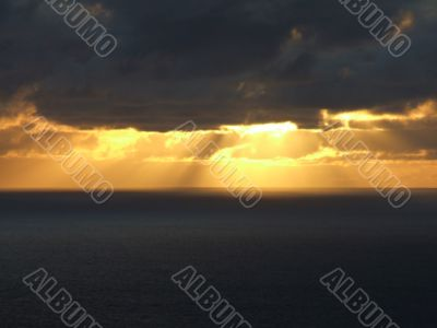 Rays of sun passing trough clouds at sea side