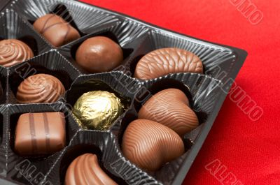 Valentines chocolates in box on red silk