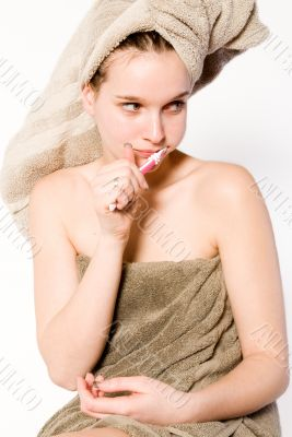 Young woman is brushing her teeth