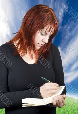 Cute redhead writing in her notebook or diary