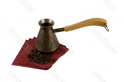 Ibrik with coffee on a serviette with coffee beans