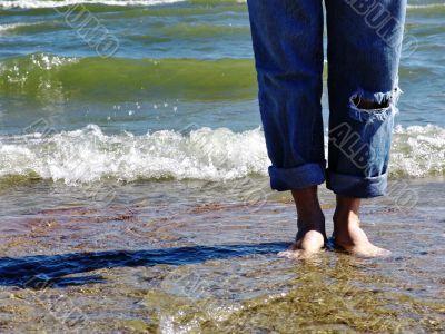 Wet bare feet standing on beach.