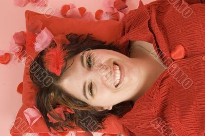 young beautiful woman laying on a red pillow