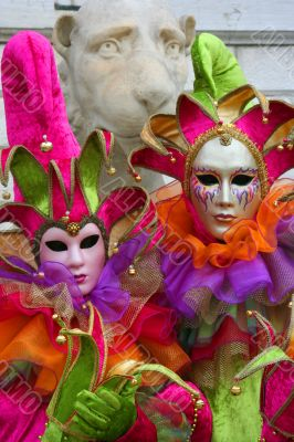 Two Venetian masks in bright, color suits