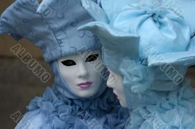 Two Venetian female masks in blue suits.