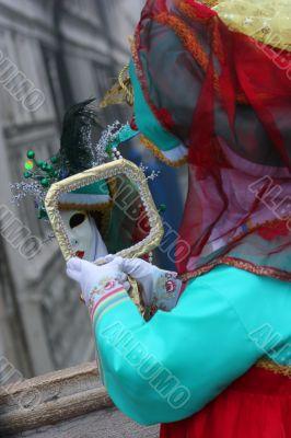 The female Venetian mask looks in a mirror.