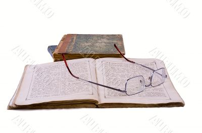 The open ancient book with glasses