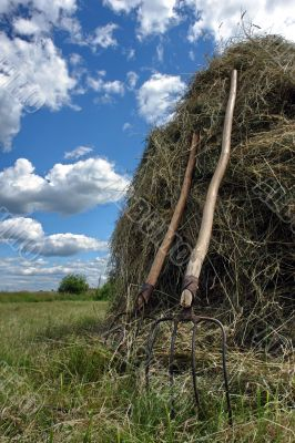stack of hay and pair of pitchfork