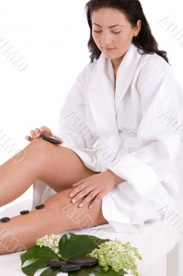 Pretty brunette giving herself a hot stone massage