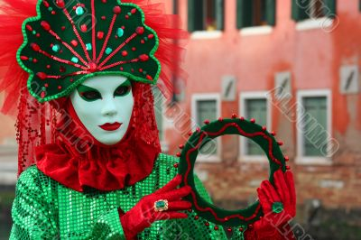 The Venetian mask in a bright green suit.