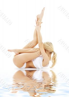 fit blond practicing yoga on sand