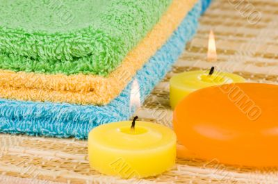 Towels of different colors soap and candles