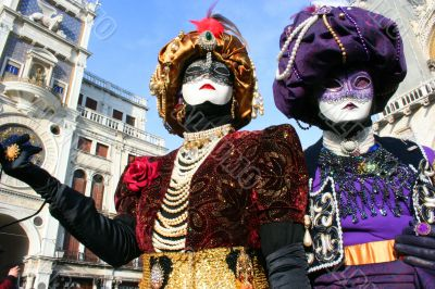 Two Venetian masks in suits.
