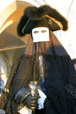 The Venetian mask in a black suit.