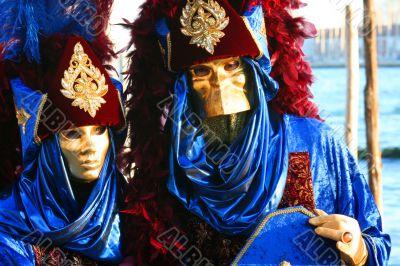 Gold masks in dark blue suits.