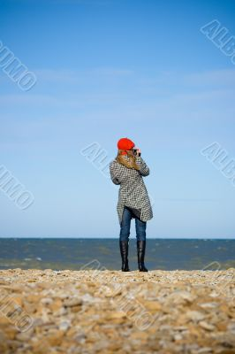 Girl standing on the beach and recording video