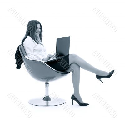 monochrome businesswoman with laptop in chair