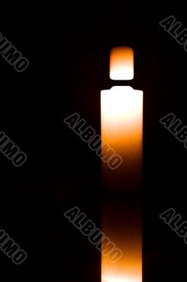 Light candle isolated on black
