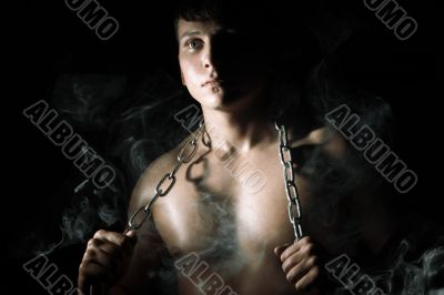 Muscular man with chain and smoke