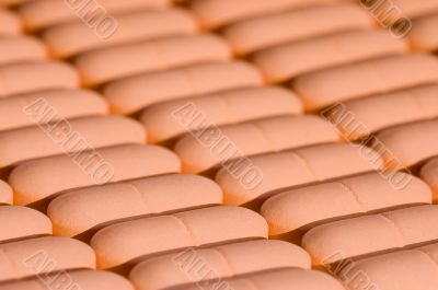 Rows of pink pills over white