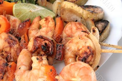 Grilled prawns on bamboo sticks served with salad and grilled ve