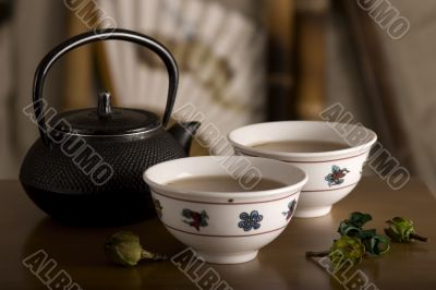 The Chinese teapot, two cups and fruit on table
