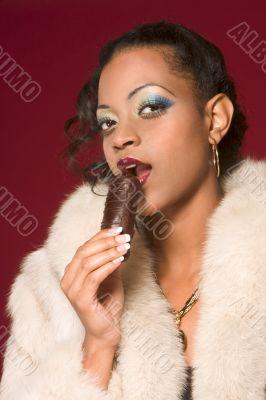 Girl in fur coat eat chocolate