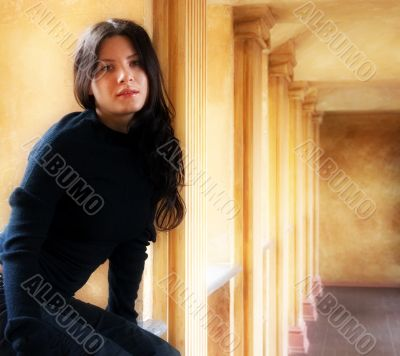 The girl sits at a window in a hall