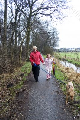 grandmother and grandchild walking with the dog