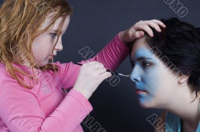 young girl is painting females face