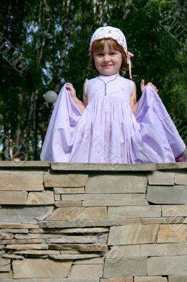 child in gown standing on wall