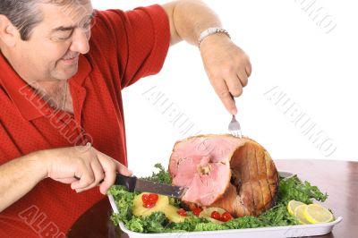 man slicing a ham